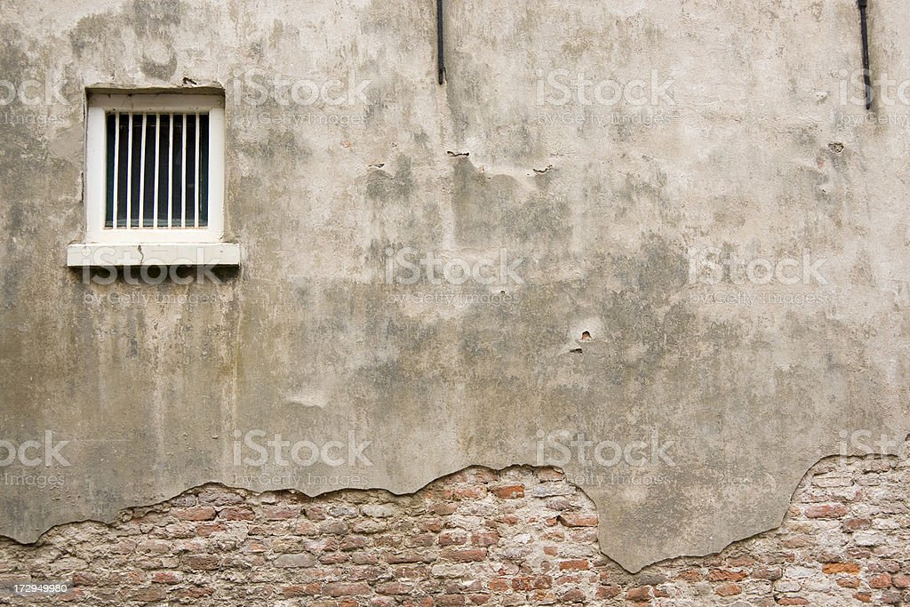 Weathered prison wall with a grilled white window stock photo
