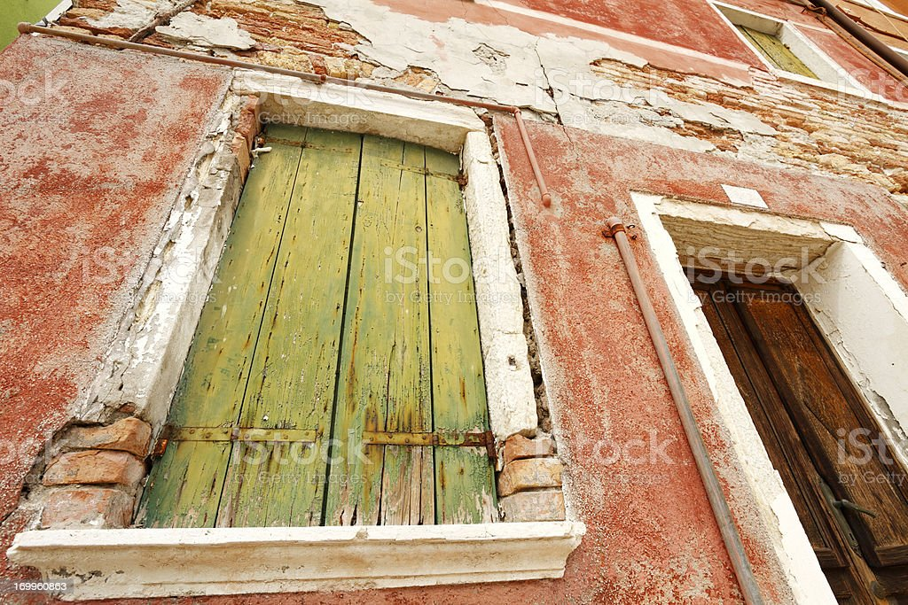 Weathered red facade with green wooden shutters royalty-free stock photo