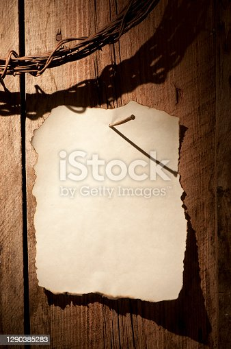 A barnwood wall with a sheet of weathered parchment paper nailed to the wall with a square nail. A partial coil of barbed wire hangs above in upper corner. Dramatic lighting