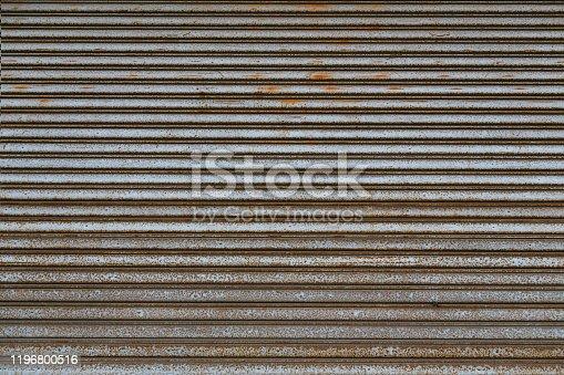 Weathered stainless steel roll up door. Rusty iron gate. Metal roller door. Metallic roller shutter door background