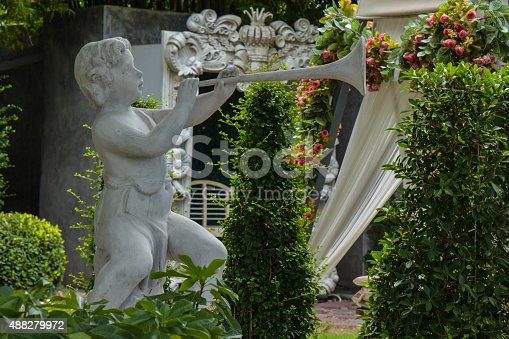 istock Weathered statue of an infant angel in garden 488279972
