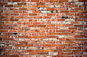 Weathered texture of dark brown and red brick wall background.