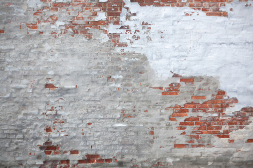 Weathered unfinished brick and cement wall.
