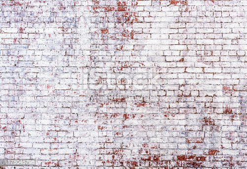 An old, distressed brick wall, with fading painted white wash.