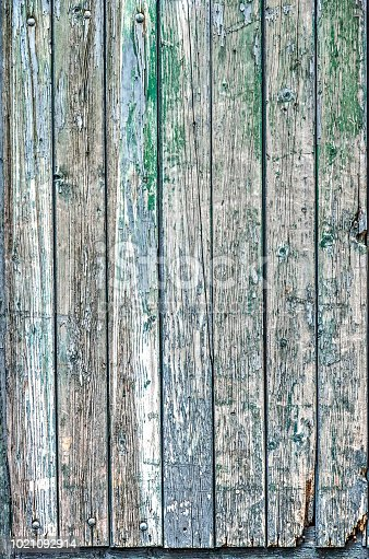 Part of a wooden door with vertical planks and peeling paint in shades of green, blue, white and brown