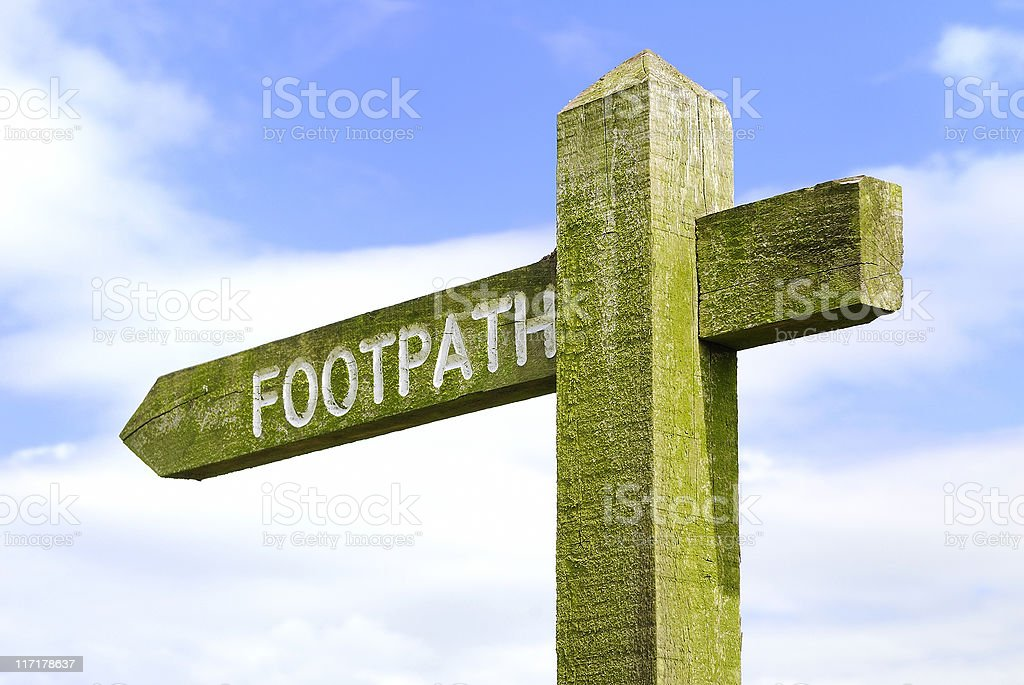 Weathered wooden footpath direction sign with blue sky and clouds royalty-free stock photo