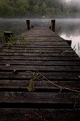 Weathered Wooden Jetty amongst mist in the beautiful Trossachs area of Scotland.