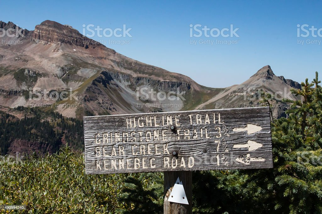 Weathered wooden sign for Highline Trail against mountain peaks stock photo