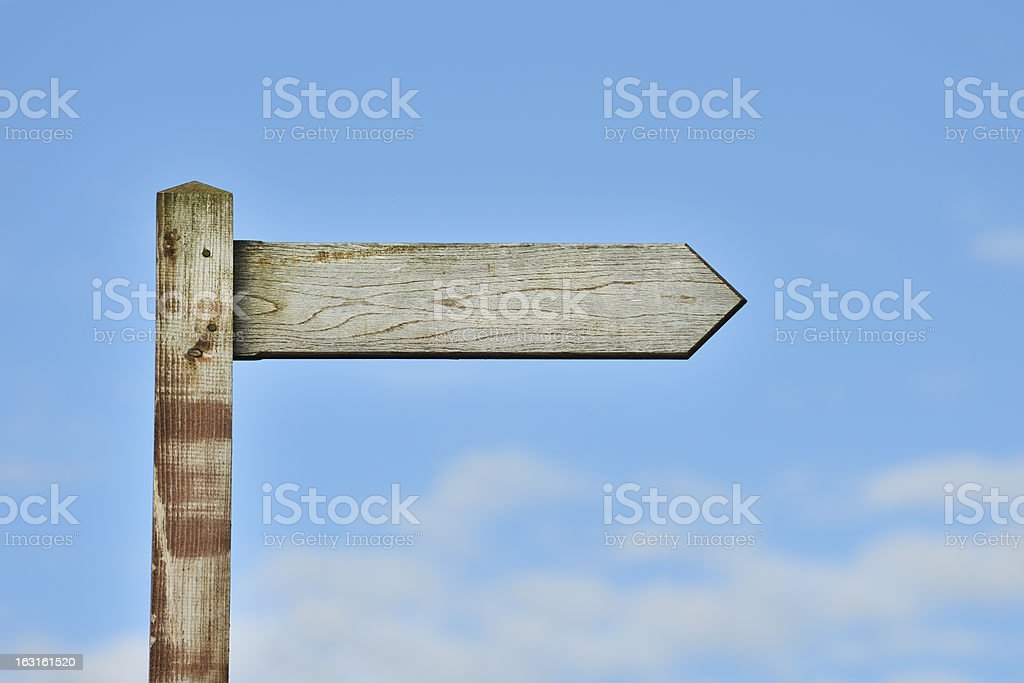 Weathered wooden sign post against blue sky stock photo