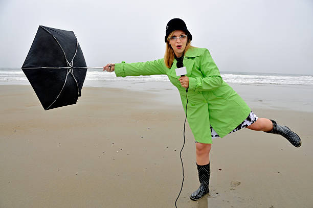 weathergirl with umbrella being blown away - mike cherim stock pictures, royalty-free photos & images