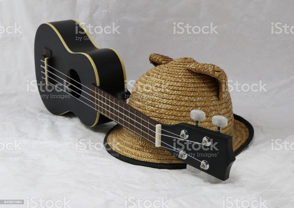 Weave hat and black ukulele on the white background. stock photo