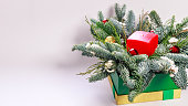 Web banner. Christmas composition with a red candle, fir branches and Christmas tree decorations on a light background. Copy space