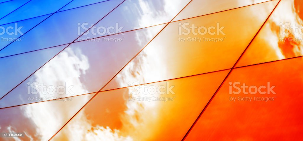 Web banner Modern glass architecture with reflection of red and blue sunset sky. Dramatic bright color. Vintage style background. stock photo