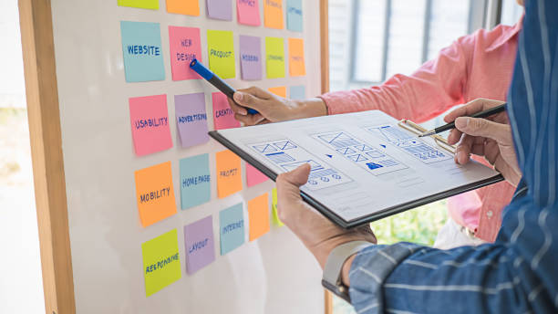 Web designer brainstorming for a strategy plan. Colorful sticky notes with things to do on office board. User experience (UX) concept. stock photo