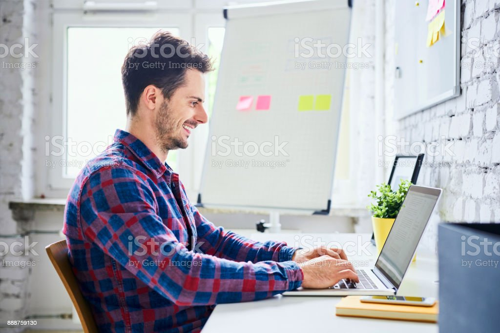 Web designer, hipster working on laptop in office stock photo