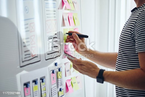 Web designer planning website ux app development with marker pen on whiteboard