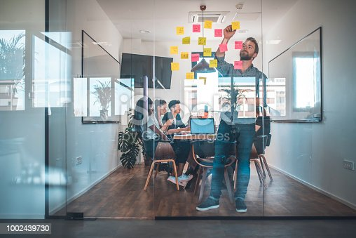 Businessman sticking adhesive note while colleagues in background. Male web designer is seen through glass wall. He is working in office.