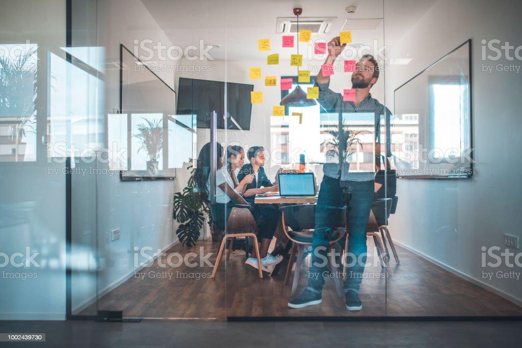 Web Designer kleben Kleber Hinweis an Glaswand – Foto