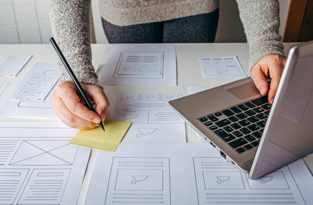 Web designer working at laptop and website wireframe sketches stock photo