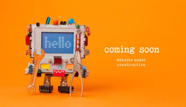 Web site under construction Coming Soon template page. Toy robot with hand wrench and pliers. Orange background - foto stock