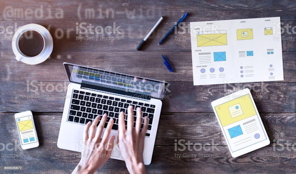 Webdesigner skizzieren ansprechende Website Drahtmodell mit Laptop, Smartphone und tablet Lizenzfreies stock-foto