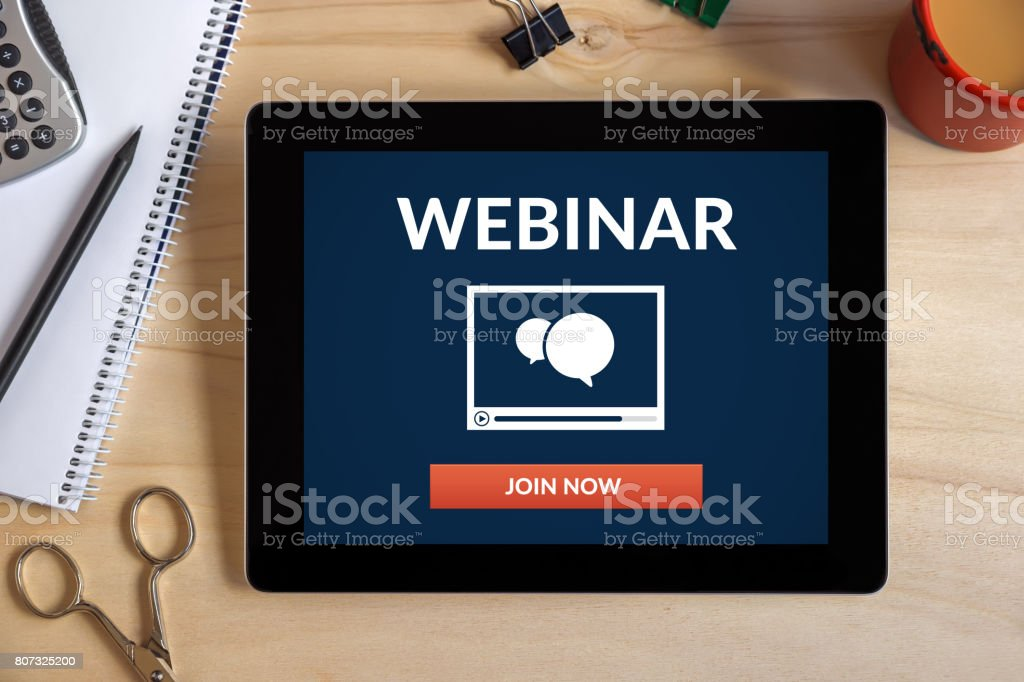 Webinar concept on tablet screen with office objects on wooden desk stock photo