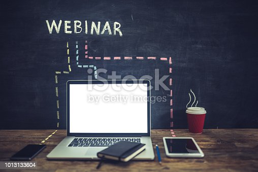 Webinar word hand written on blackboard connected with doted lines to many gadgets on a wooden desk