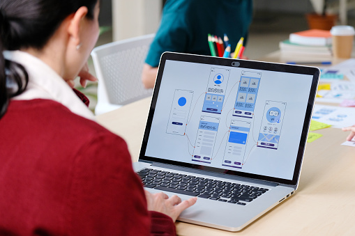 Website designer, Creative planning phone app development template layout framework wireframe design, User experience concept, Young asian woman UX designer working on smartphone application at office