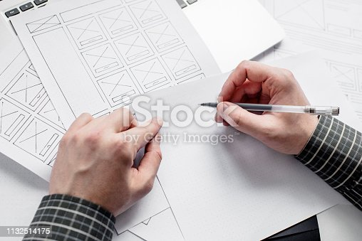 istock UX website designer drawing wireframe sketch of prototype, framework, layout future project. Creative user experience concept website template. Designer workspace 1132514175