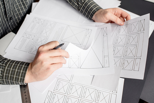 UX website designer drawing wireframe sketch of prototype, framework, layout future project. Creative user experience concept website template. Designer workspace