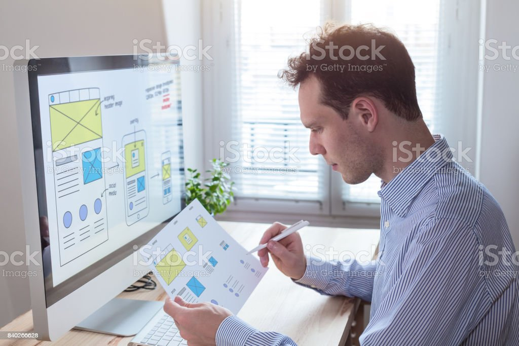 Website designer reading client specification, sketching responsive wireframe layout design stock photo