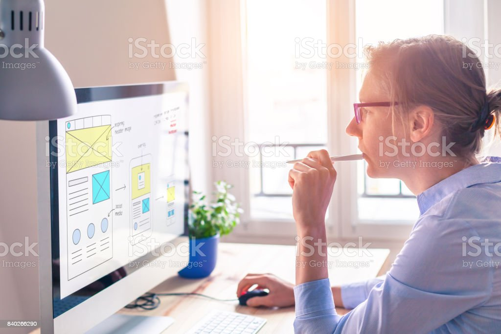 Website front end designer sketching wireframe layout mockup, bright office stock photo