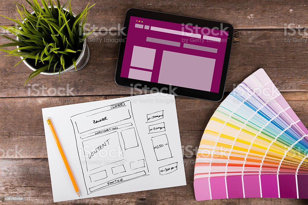 website wireframe sketch and digital tablet on wooden table stock photo