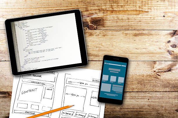 website wireframe sketch and programming code on digital tablet stock photo