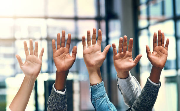 We'd like to volunteer Cropped shot of a group of unrecognizable businesspeople raising their hands verbaasd stock pictures, royalty-free photos & images