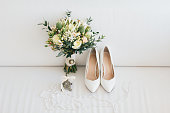 Wedding accessories: shoes and bouquet of the bride