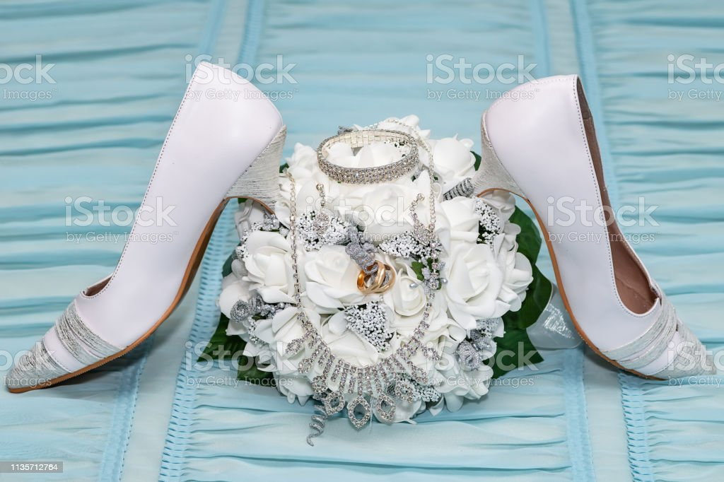 Wedding accessories. Two wedding rings in a bridal bouquet, earrings,...