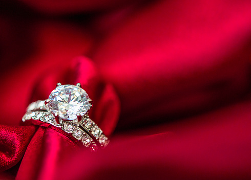 Wedding and engagement rings in rich red satin stock photo