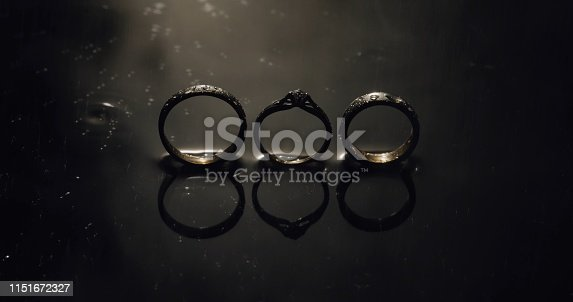 istock Wedding and engagement rings lying on dark water surface shining with light 1151672327