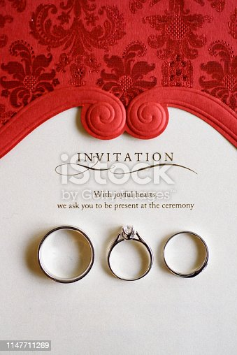 Wedding and engagement rings macro shot from top with wedding invitation background