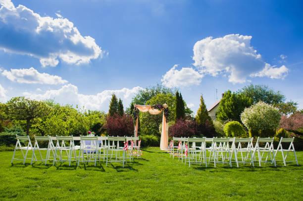 hochzeit bogen und weiße stühle auf natur hintergrund - grüne wald hochzeiten stock-fotos und bilder