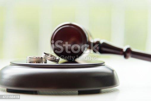 istock Wedding bands sitting on a judges gavel 472155419