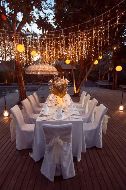 hochzeits-bankett oder gala-dinner mit girlanden geschmückt. festliche tafel einrichten dekoration für hochzeit, party oder veranstaltung - grüne wald hochzeiten stock-fotos und bilder