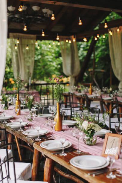 hochzeit. bankett. die festliche tafel für gäste, dekoriert mit einer komposition aus weißen und rosafarbenen blumen und grün, es gibt kerzen, serviert mit geschirr n aus holz gartenhaus. - tischdeko goldene hochzeit stock-fotos und bilder
