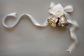 Silver wedding bells tied with a white ribbon and adorned with pearls and flowers on a silver background