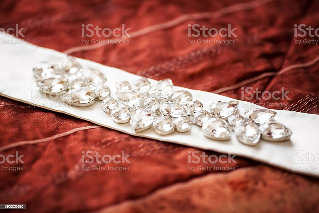 Wedding belt decorated with jewelry on red sofa. Marriage concept Стоковые фото Стоковая фотография
