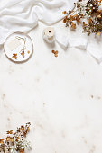 istock Wedding, birthday stationery styled stock photo. White table runner, porcelain plate with stamp, golden clips, silk ribbon, dry hydrangea, gypsophila flowers. Marble stone background. Vertical flatlay 1163519316