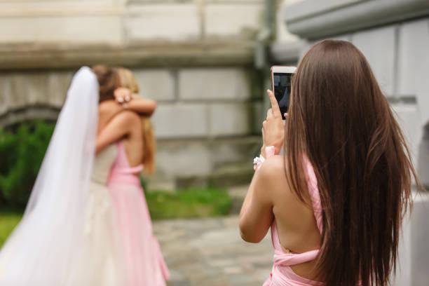 foto der braut und brautjungfer hochzeit blogger machen, spaß zu haben, nach der trauung. glückliche ehe-konzept - hochzeitskleider online stock-fotos und bilder