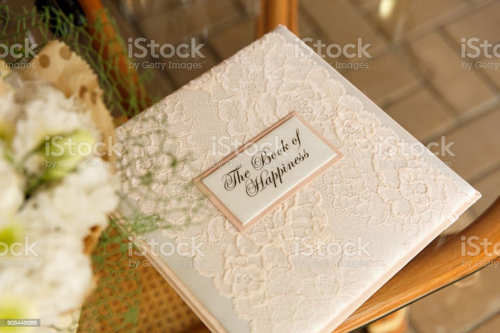 Wedding book for writing best wishes on wedding day. Album for marriage memories for bride and groom. Scrapbook with inscription ''The Book of Happiness'' stock photo