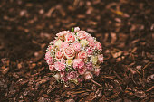 Wedding bouquet from pink roses among pine tree bark